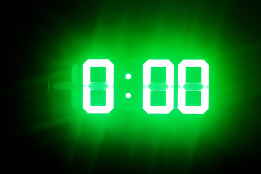 istock Green glowing digits in the dark show 0:00. Midnight time. 1165346815