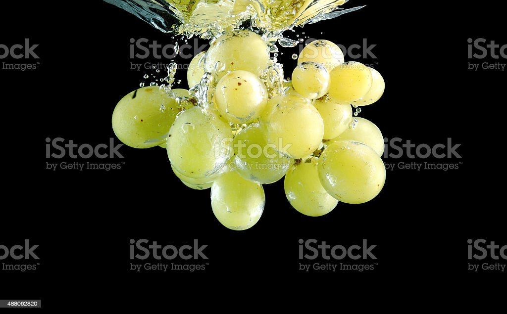 Green grape falling into water at black background stock photo
