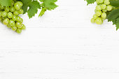 Green grape with leaves on wooden table. Top view flat lay with copy space for your text