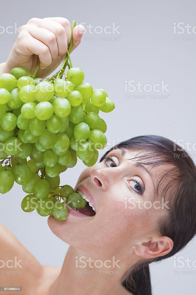 Green grapes eating woman with grape between teeth royalty-free stock photo