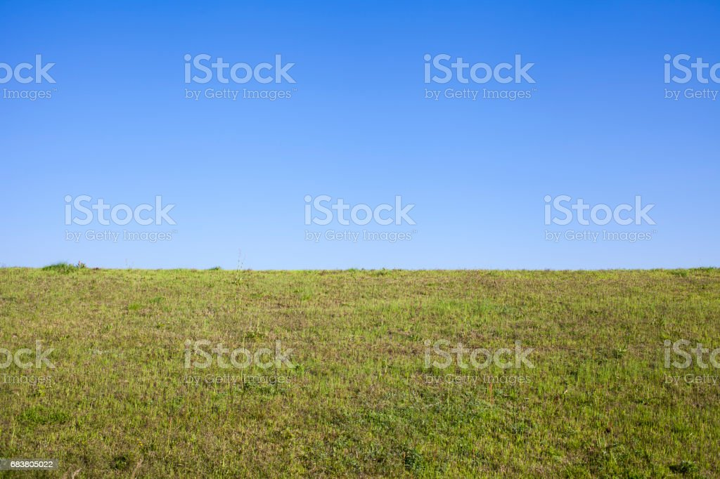green grass bank and the blue sky stock photo