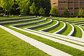 this photo is of a Green Grass Lawn with Steps at a Park. the landscape is very scenic. the lawn is designed in a modern design similar to amphitheater with rows of grassy seats. there are buildings in the background. the trees have green leaves. this photo was taken during the spring or summer. the lighting is natural warm sunlight.