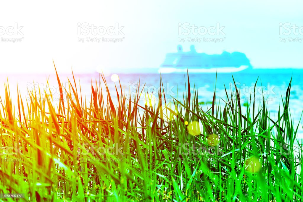 Grüner Rasen mit einer Blurried unkonzentriert Kreuzfahrt Schiff zu Sonnenuntergang Horizont entfernt. Urlaub-Konzeption. RGB mit einer bunten Blendenfleck abgeschwächt - Lizenzfrei Bernstein Stock-Foto