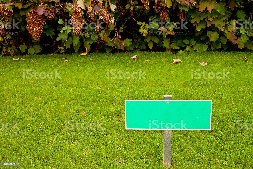 Green grass with a sign and bush, horizontal shot royalty-free stock photo
