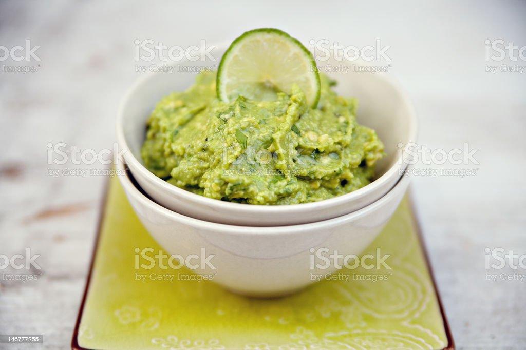 Green guacamole in a white bowl stock photo