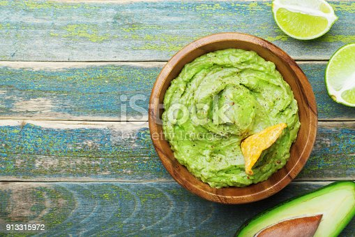 istock Green guacamole with  ingredients avocado, lime and nachos on wooden vintage table top view. 913315972