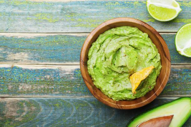 guacamole verde com ingredientes abacate, limão e nachos em cima da mesa de madeira vintage vista. - guacamole - fotografias e filmes do acervo
