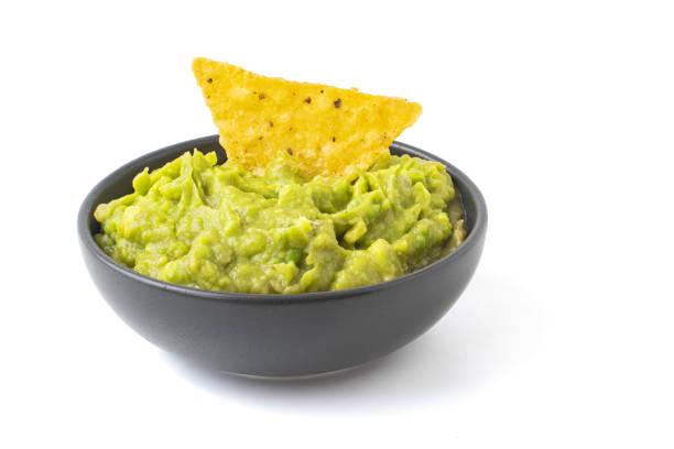 guacamole verde com os nachos na bacia escura isolada no fundo branco - guacamole - fotografias e filmes do acervo