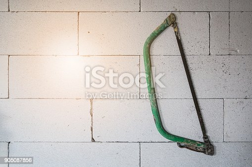 905087856istockphoto Green hand saw hang on ightweight autoclaved aerated concrete wall background, construction concept 905087856