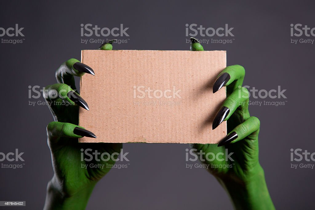 Green hands with black nails holding empty piece of cardboard stock photo