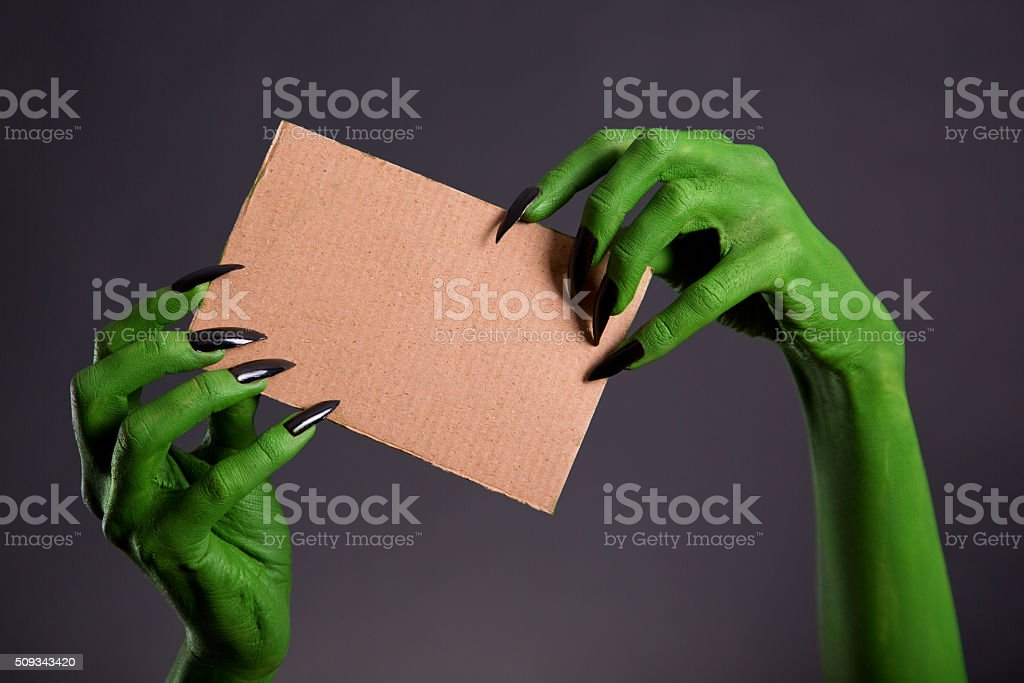 Green hands with long black nails holding cardboard stock photo