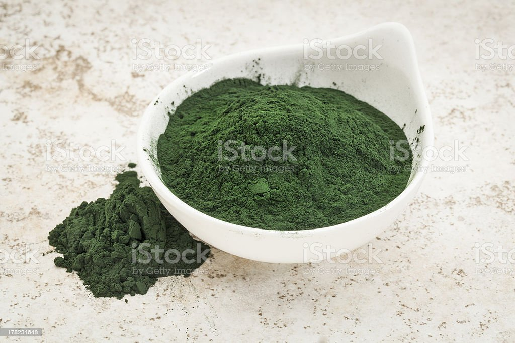 Green Hawaiian spirulina powder in a large white bowl​​​ foto