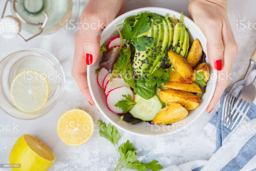 Green healthy vegan breakfast salad with baked potato, avocado and radish stock photo