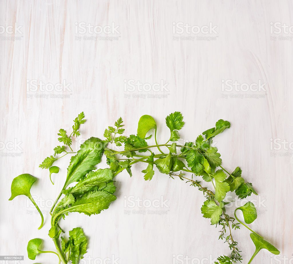 green herbs on white wooden table, food background, top view stock photo