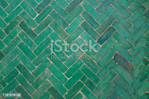 Close up shot of green herringbone brick flooring tile