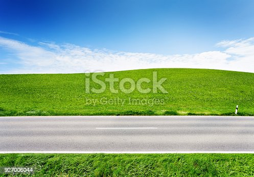 istock Green hill and asphalt road, side view 927006044