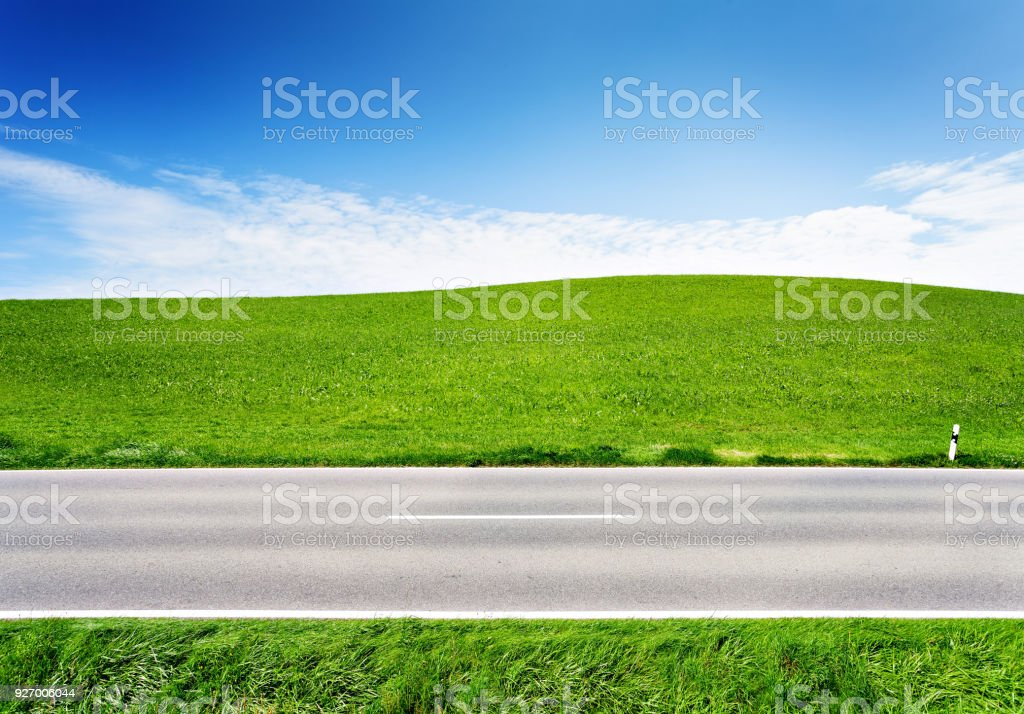 Green hill and asphalt road, side view stock photo