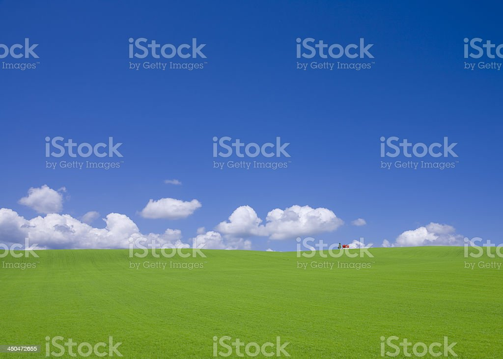 Green hill and red roof house stock photo