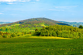 istock Green hill in the middle of sunny spring landscape. Javornik Mountain near Liberec, Czech Republic 957476988