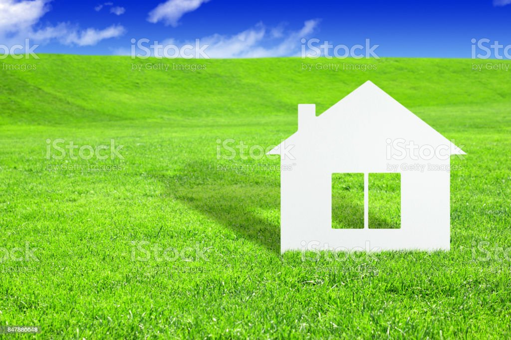 Green home concept, paper house on field stock photo