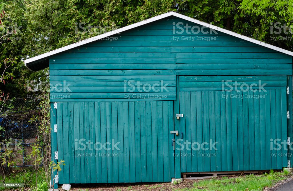 Green homebuilt garage on a slope with uneven padlocked doors - Royalty-free Building Exterior Stock Photo