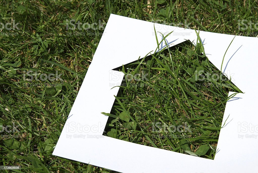 Green Housing Green Housing - Cutout of a house on a grass background Architecture Stock Photo