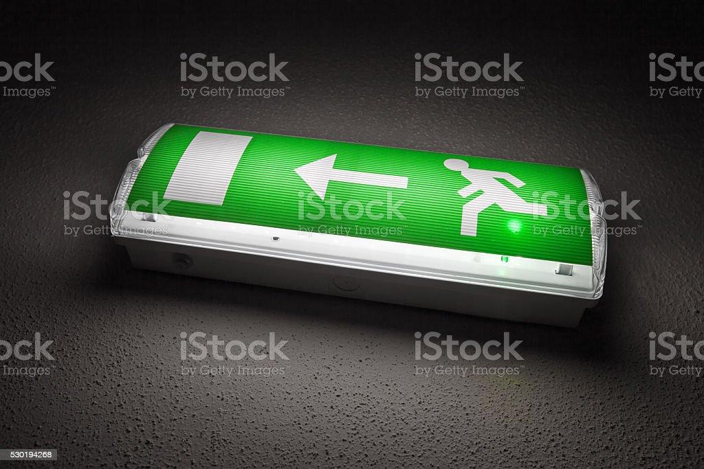 Green illuminated emergency exit sign in dark stock photo