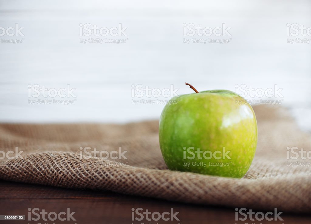 Green juicy apple on sacking. The concept of healthy eating and vegetarianism. royalty-free stock photo