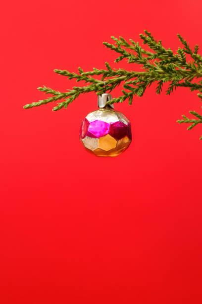 Grüner Wacholderzweig mit einem Weihnachtsspielzeug auf rotem Grund. Neujahrshintergrund. – Foto