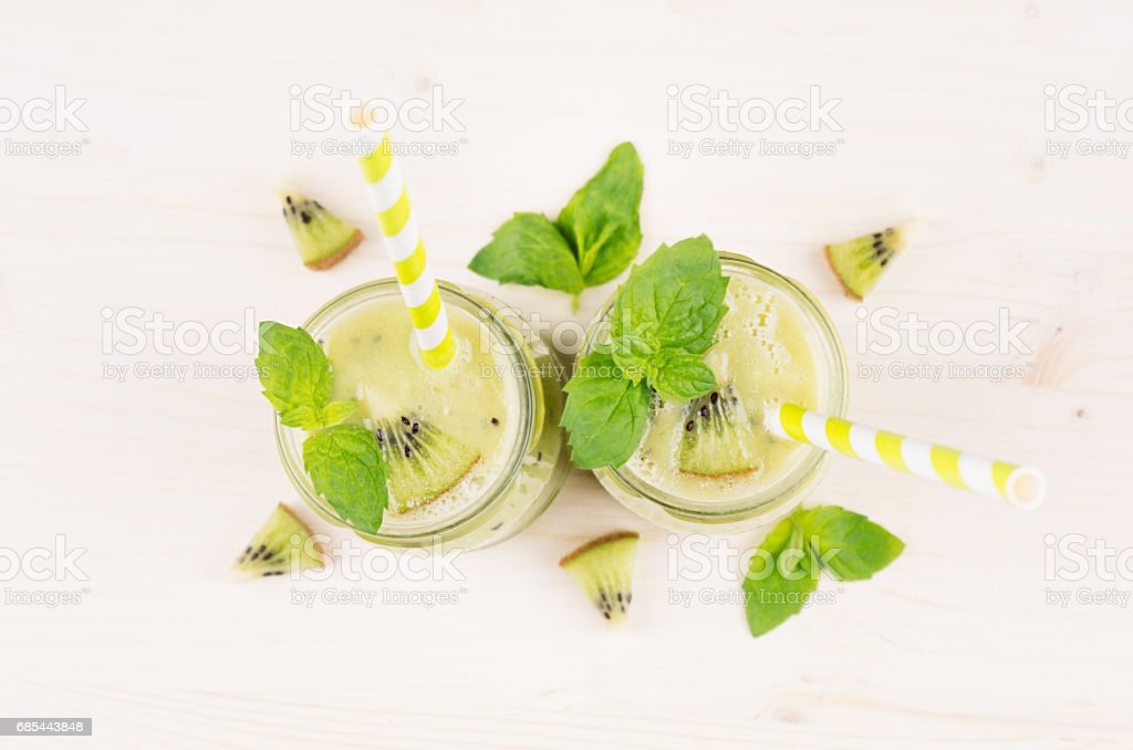 Green kiwi fruit smoothie in glass jars with straw, mint leaf, cut ripe berry, close up, top view. White wooden board background. foto de stock royalty-free
