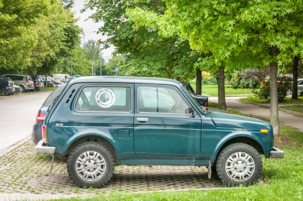 grün lada niva 4 x 4 off road auto auf der straße geparkt. - lada niva stock-fotos und bilder