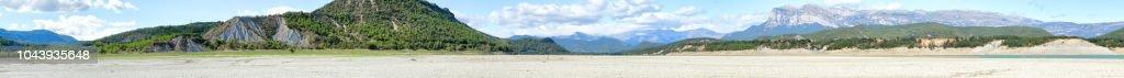 Un verde paisaje del lago artificial Mediano en el Pirineo Aragonés Español visto desde dentro del lago, con pasto verde fresco, cielo azul con nubes, azul agua y denso bosque en las montañas - foto de stock