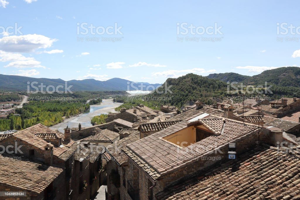 Un verde paisaje del lago artificial Mediano en el Pirineo Aragonés Español visto desde el tradicional pueblito de Ainsa, con un panorama urbano de los tejados de la ciudad casas - foto de stock