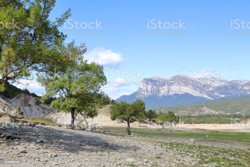 Un verde paisaje del lago artificial Mediano en el Pirineo Aragonés Español visto desde dentro del lago, con pasto verde fresco, cielo azul con nubes, agua azul y la montaña del macizo de Peña montañesa en el fondo - foto de stock