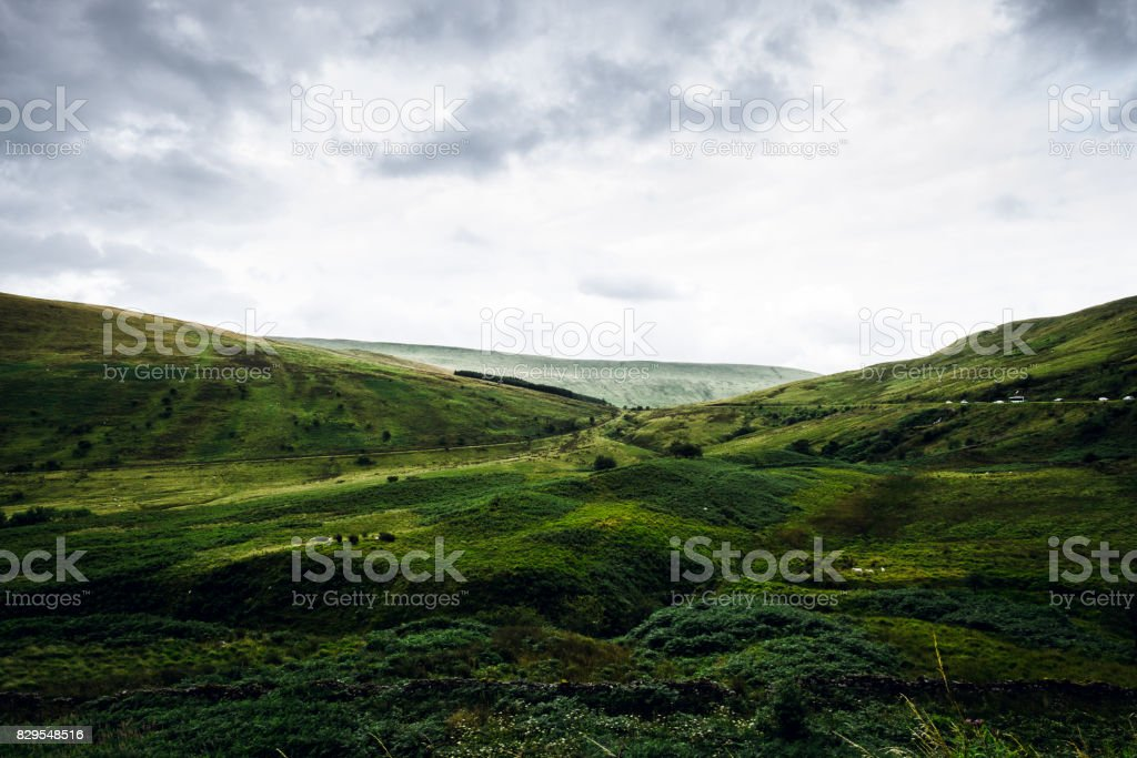 Green landscape with sheep and moody sky viewed from Pen y Fan mountain, Wales, Brecon Beacons National Park stock photo