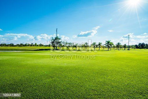green lawn an blue sky in tropical golf course
