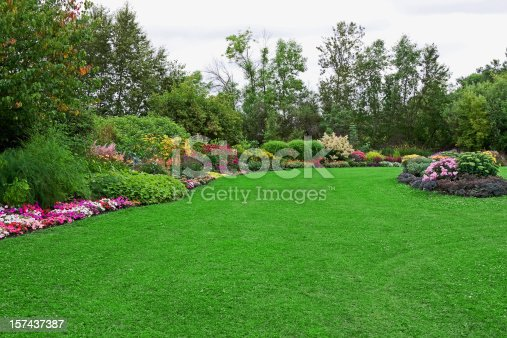 Green lawn (with a bit of clover) in a colorful landscaped formal garden.