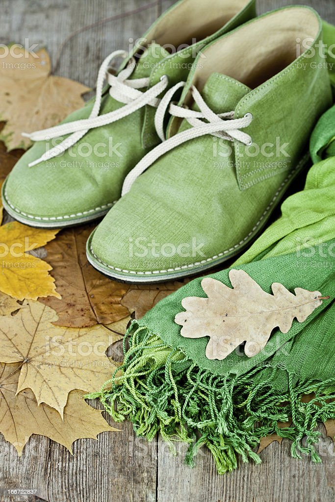 green leather boots, scarf and yellow leaves royalty-free stock photo