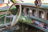 Green leather, wood and chrome interior of a classic american luxury oldtimer car. Steering wheel, radio, speedometer and a hairy dice.
