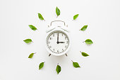 Green leaves around white alarm clock on light table background. Time change concept. Closeup. Top down view.
