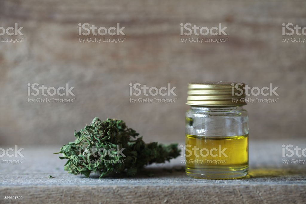 Green leaves of medicinal cannabis with extract oil on a wooden table. alternative medicine stock photo