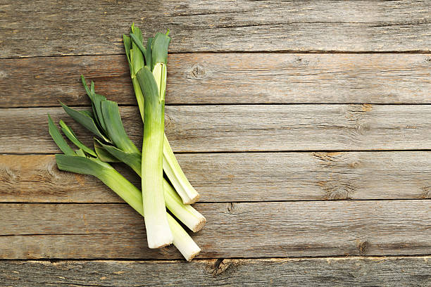 Green leeks on a grey wooden table Green leeks on a grey wooden table leek stock pictures, royalty-free photos & images