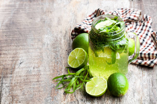 green  lemonade with tarragon and lime on wooden background - tarragon stock photos and pictures