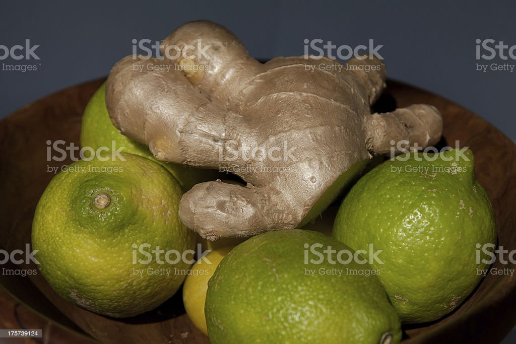 Green lemons and ginger in a wooden bowl royalty-free stock photo