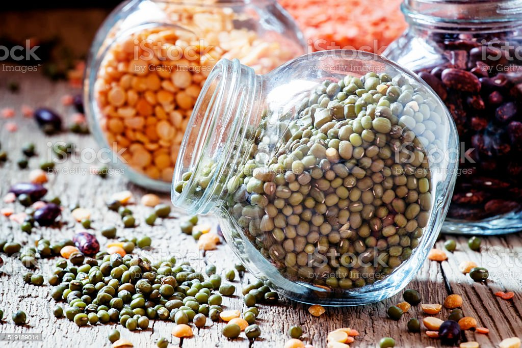 Green lentils in a glass jar, mix beans stock photo
