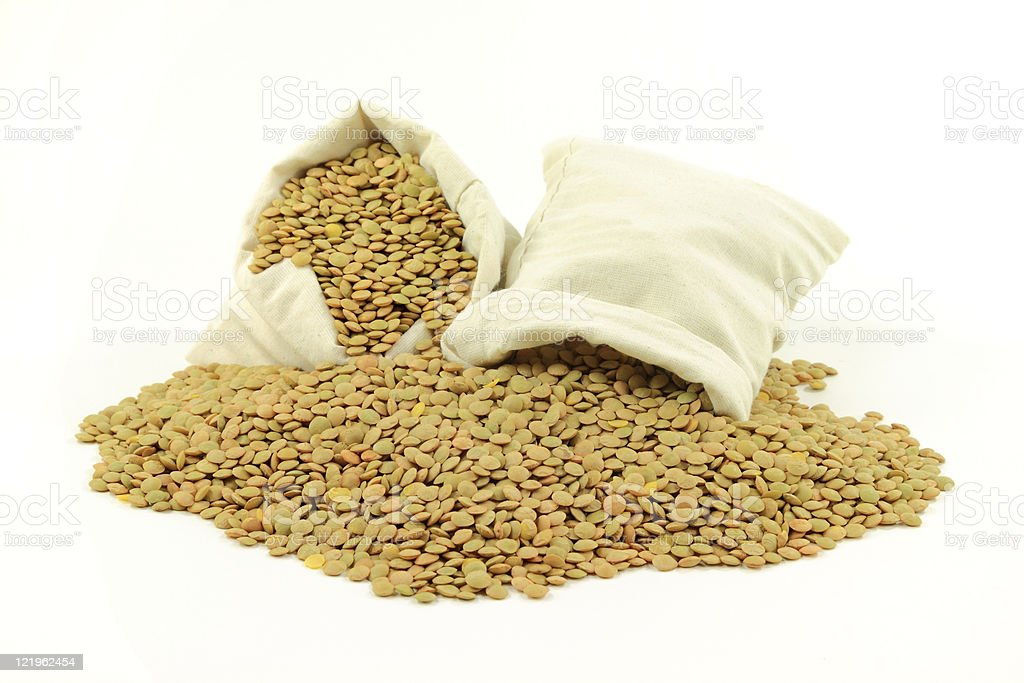Green lentils in fabric bags and on pile royalty-free stock photo