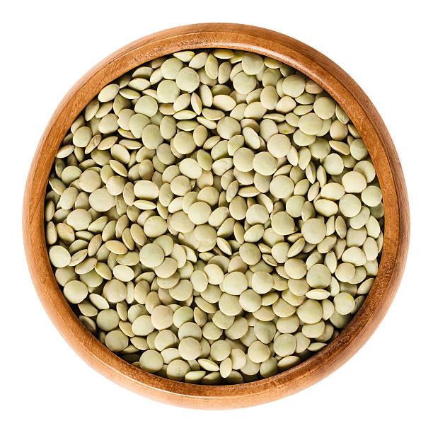 Green lentils in wooden bowl over white stock photo