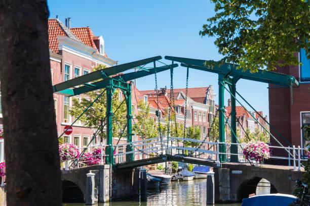 green lifting bridge called Kerkbrug, across canal, Leiden,  The Netherlands green bridge over water, Leiden, Holland leiden stock pictures, royalty-free photos & images