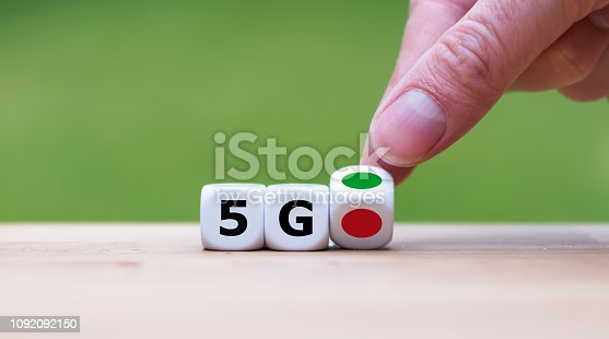 istock Green light for 5G (fith generation wireless). Hand is turning a dice and changes the color of a dot from red to green symbolizing the start of 5G. 1092092150