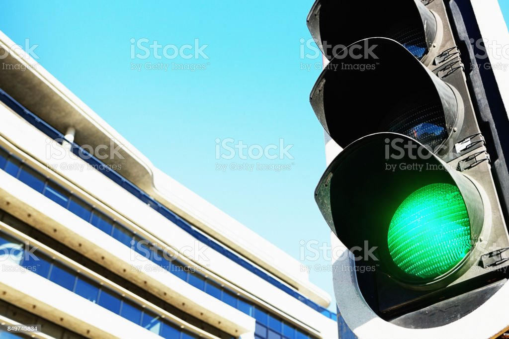 Green light for business: green traffic signal with office block stock photo